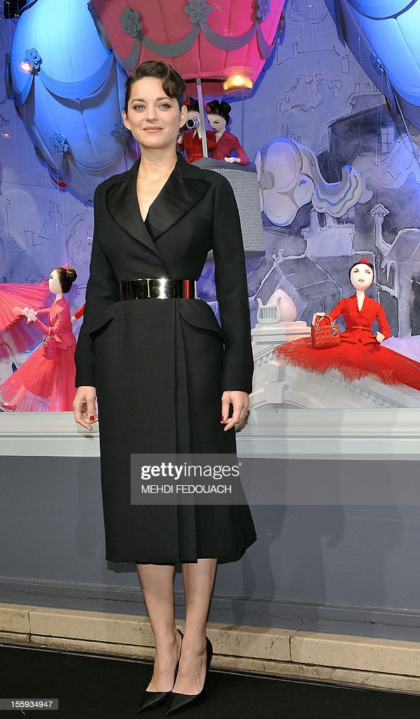 French actress Marion Cotillard poses in front of the Printemps department store to mark the inauguration of the new Christmas window display on November 9, 2012, in Paris. AFP PHOTO / MEHDI FEDOUACH