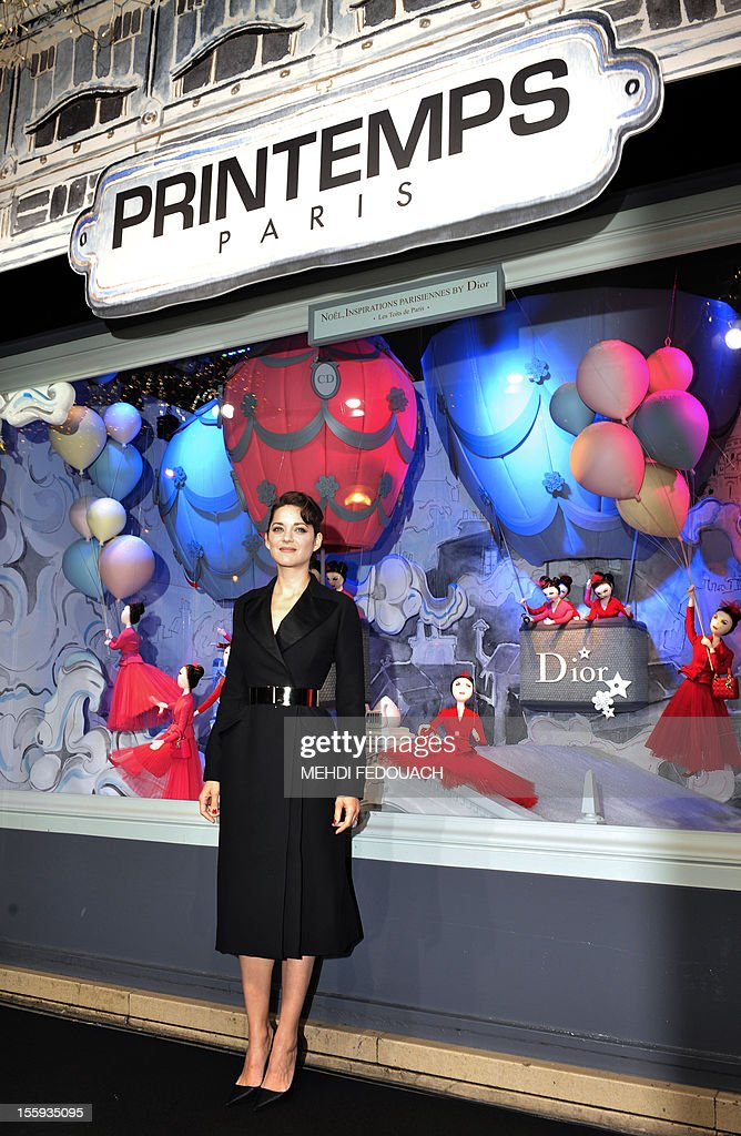 French actress Marion Cotillard poses in front of the Printemps department store to mark the inauguration of the new Christmas window display on November 9, 2012, in Paris.