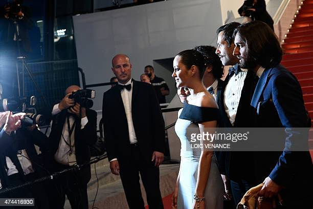 French actress Marion Cotillard poses with French producer Dimitri Rassam and French actor Laurent Lafitte before leaving the Festival palace after...