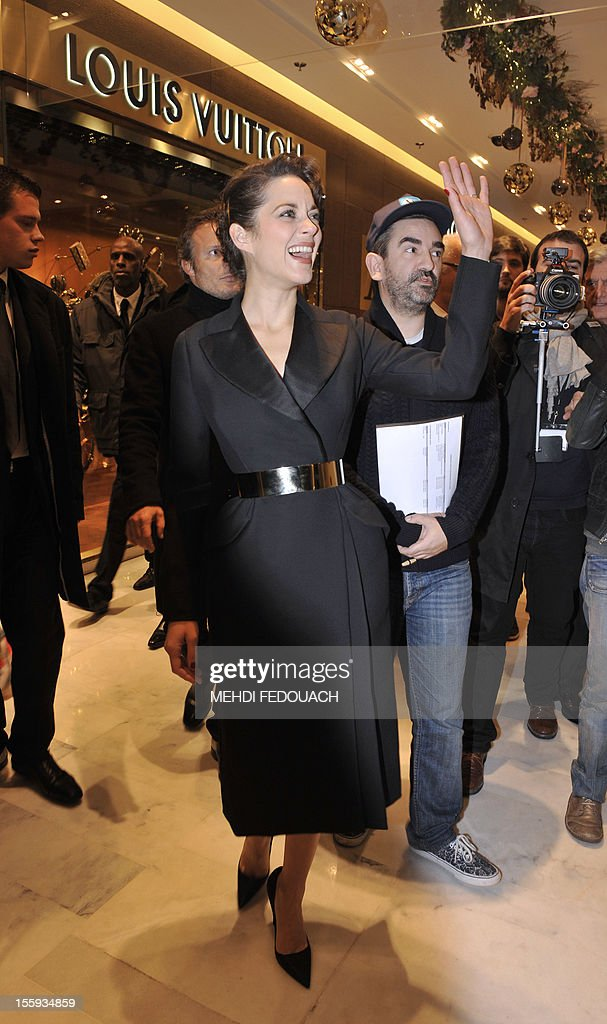 French actress Marion Cotillard walks inside the Printemps department store during the inauguration of the new Christmas window displays on November 9, 2012, in Paris. AFP PHOTO / MEHDI FEDOUACH