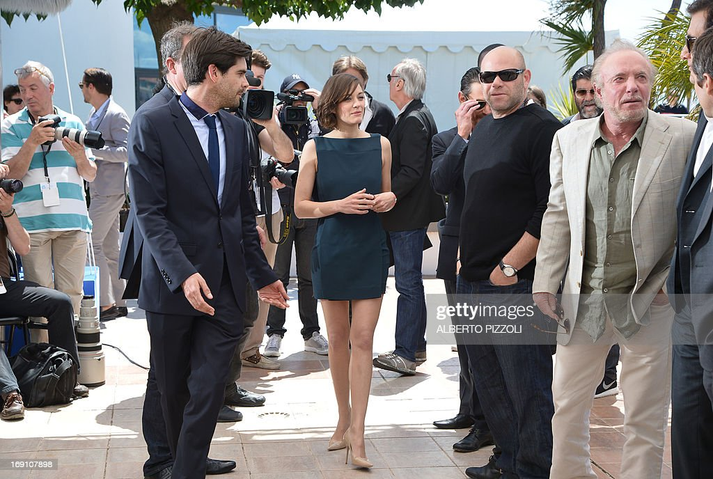 French actress Marion Cotillard (C) walks on May 20, 2013 past US actors Domenick Lombardozzi (4thR) and James Caan (3rdR) as she arrives to attend a photocall for the film 'Blood Ties' presented Out of Competition at the 66th edition of the Cannes Film Festival in Cannes. Cannes, one of the world's top film festivals, opened on May 15 and will climax on May 26 with awards selected by a jury headed this year by Hollywood legend Steven Spielberg. AFP PHOTO / ALBERTO PIZZOLI