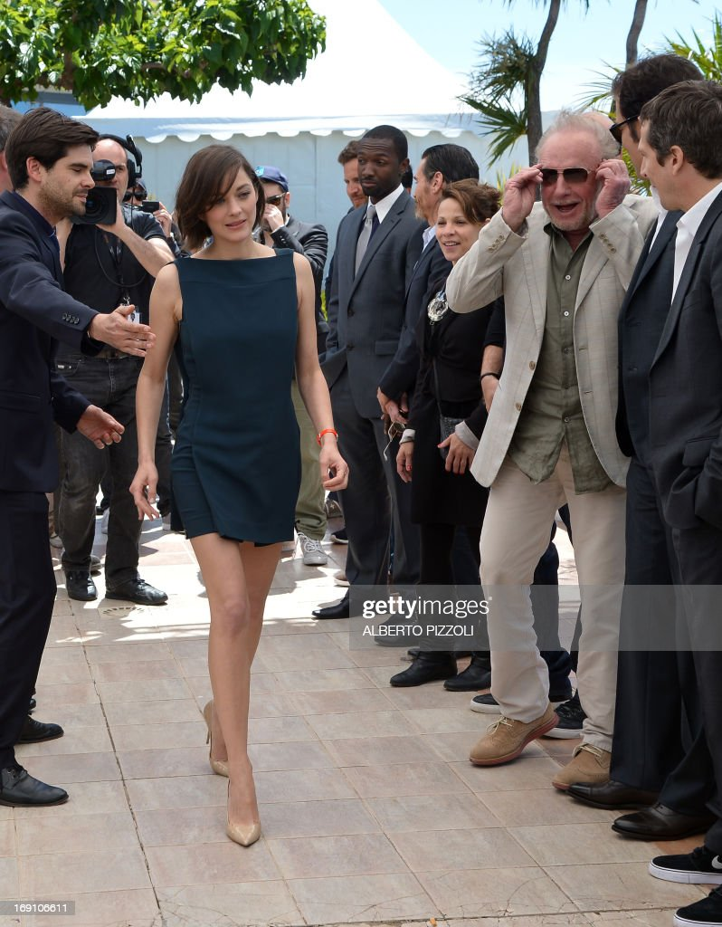 French actress Marion Cotillard (C) walks past US actor James Caan (3rdR) on May 20, 2013 as she arrives for a photocall for the film 'Blood Ties' presented Out of Competition at the 66th edition of the Cannes Film Festival in Cannes. Cannes, one of the world's top film festivals, opened on May 15 and will climax on May 26 with awards selected by a jury headed this year by Hollywood legend Steven Spielberg. AFP PHOTO / ALBERTO PIZZOLI