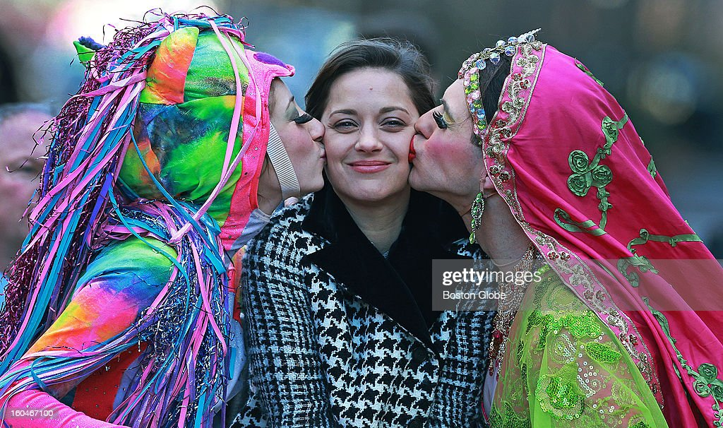 French actress Marion Cotillard was named the 2013 Hasty Pudding Theatricals Woman of the Year today. She rode in a convertible for the traditional parade through the streets near Harvard Square. She then was roasted on stage in Farkas Hall, where she was presented with the coveted pudding pot. Here she gets kisses from Renee Rober, left, President of the Hasty Pudding Theatricals, and Ben Moss, right, Composer and Cast Vice President as they drive during the parade.