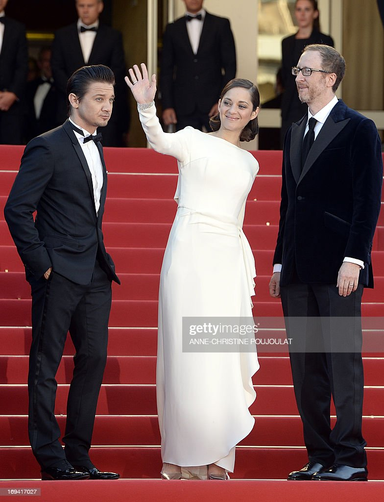 French actress Marion Cotillard (C) waves on May 24, 2013 as she arrives with US actor Jeremy Renner (L) and director James Gray for the screening of the film 'The Immigrant' presented in Competition at the 66th edition of the Cannes Film Festival in Cannes. Cannes, one of the world's top film festivals, opened on May 15 and will climax on May 26 with awards selected by a jury headed this year by Hollywood legend Steven Spielberg.