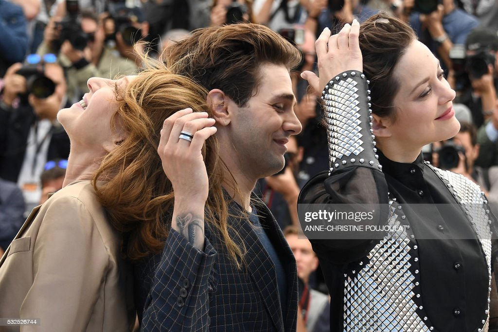 TOPSHOT - (FromL) French actress Nathalie Baye, Canadian director Xavier Dolan and French actress Marion Cotillard pose on May 19, 2016 during a photocall for the film 'It's Only The End Of The World (Juste La Fin Du Monde)' at the 69th Cannes Film Festival in Cannes, southern France. / AFP / ANNE