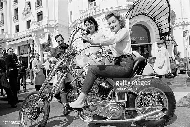 French actress Pauline Lafont rides a chopper motorcycle as her mother French actress Bernadette Lafont stands behind on March 14 1980 during the...