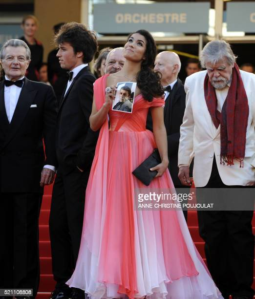 French actress Sabrina Ouazani holds a portrait of an actor in the film who recently died as she arrives of the screening of 'Des Hommes et des...