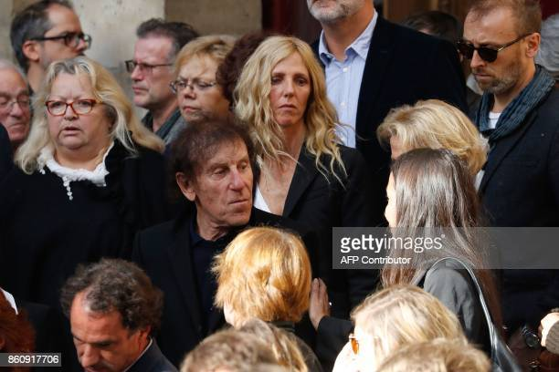 French actress Sandrine Kiberlain singer Alain Souchon and other attendees leave after the funeral of French actor Jean Rochefort at the SaintThomas...