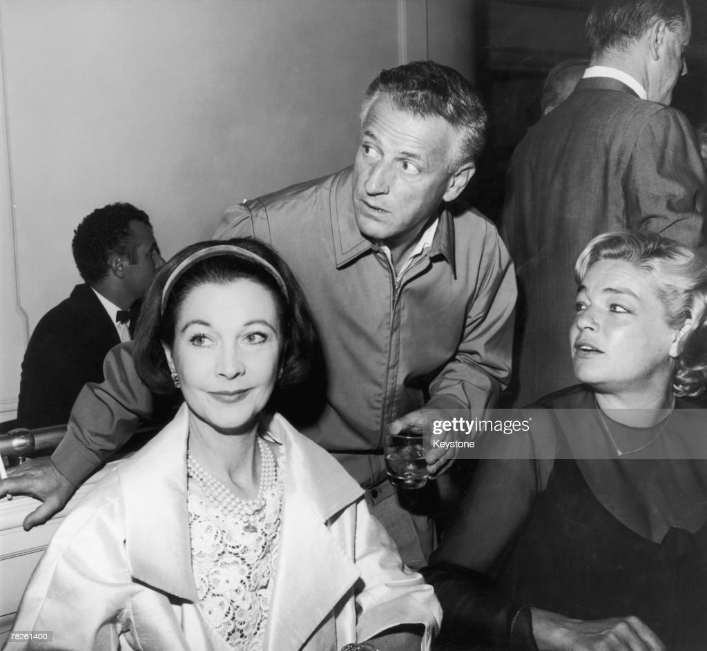 French actress Simone Signoret (1921 - 1985, right) and British actress Vivien Leigh (1913 - 1967) at a party given by American director Stanley Kramer (1913 - 2001, centre) to celebrate the completion of his film 'Ship of Fools', Hollywood, 1965.