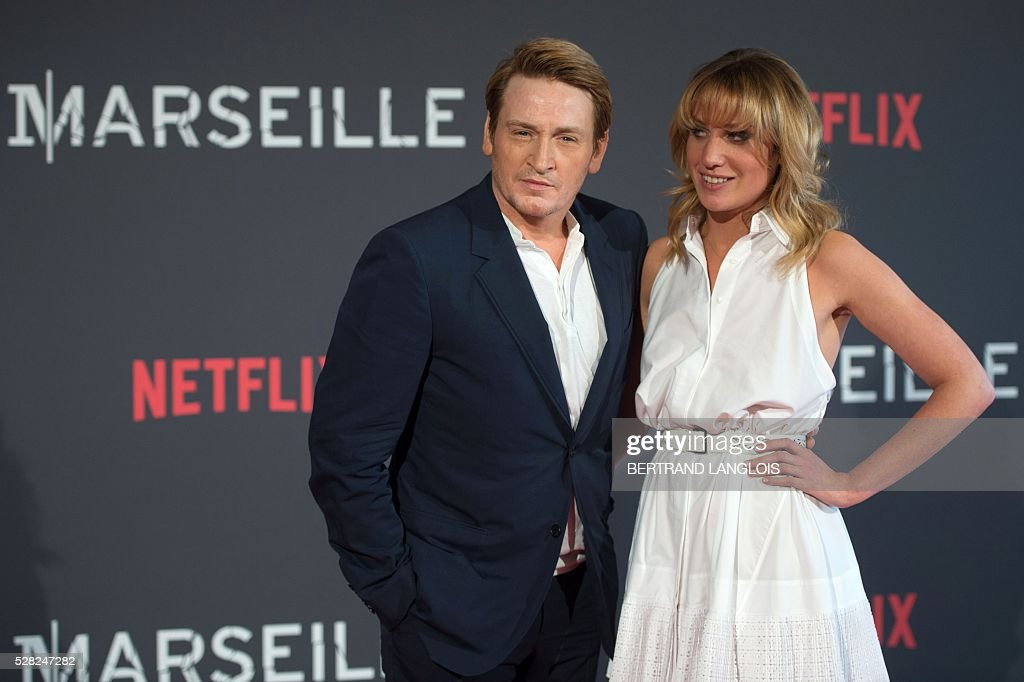 French actror Benoit Magimel (L) poses with a guest during a photocall for the premiere of the French TV show 'Marseille' broadcasted and co-produced by Netflix on May 4, 2016 in Marseille, southern France. / AFP / BERTRAND