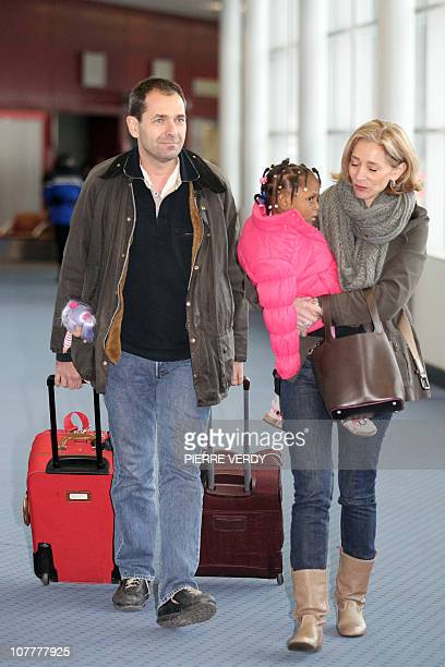French adoptive parents exit with their child fom Haiti at the RoissyenFrance airport outside Paris after their arrival on a French...