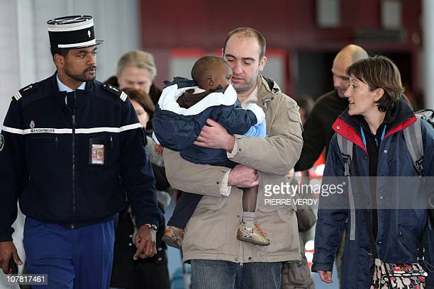 French adoptive parents exit with their children fom Haiti at the RoissyenFrance airport outside Paris after their arrival on a French...