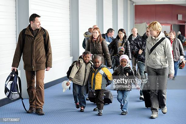 French adoptive parents exit with their children fom Haiti the RoissyenFrance airport outside Paris after their arrival on a French...