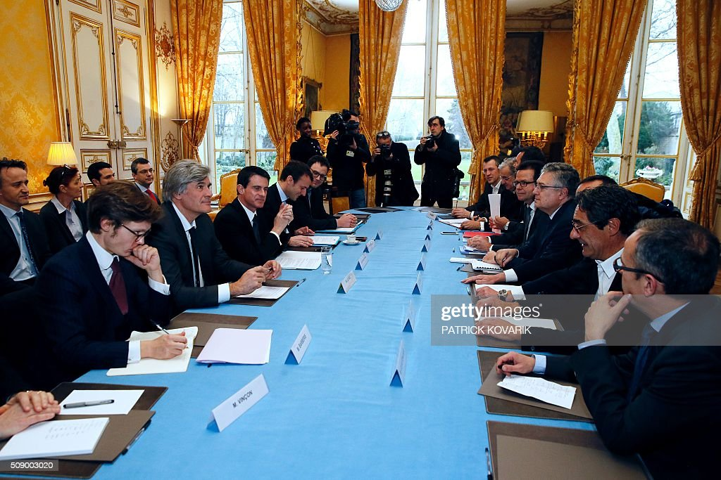 French Agriculture minister and Government spokesperson Stephane Le Foll (2nd L), French Prime Minister Manuel Valls (3rd R) and French Economy and Industry minister Emmanuel Macron (4th R) meet with CEO of French retail and supermarket group Systeme U (2nd R) and other representatives of supermarkets at the Hotel Matignon in Paris, on February 8, 2016, amid a crisis in France's agricultural sector. French farmers have carried out a string of demonstrations for nearly two weeks against the falling prices of their products, demanding structural measures to strengthen price rates. AFP PHOTO / PATRICK KOVARIK / AFP / PATRICK KOVARIK