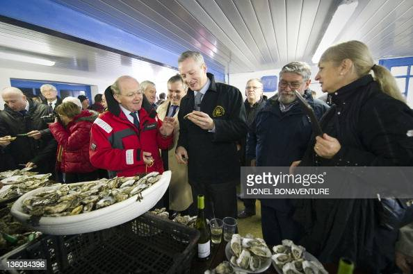 French agriculture minister Bruno Le Maire visits an oyster farmer in LocoalMendon western France on December 19 2011 to speak about pollution...