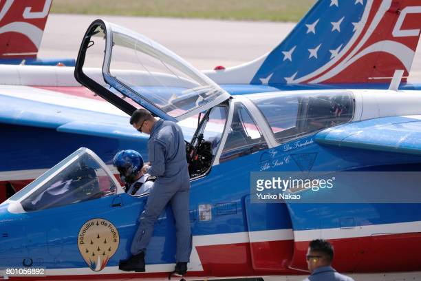 French Air Force pilot is assisted to disembark after the Patrouille de France aerial demonstration over the Le Bourget Airport on the first public...