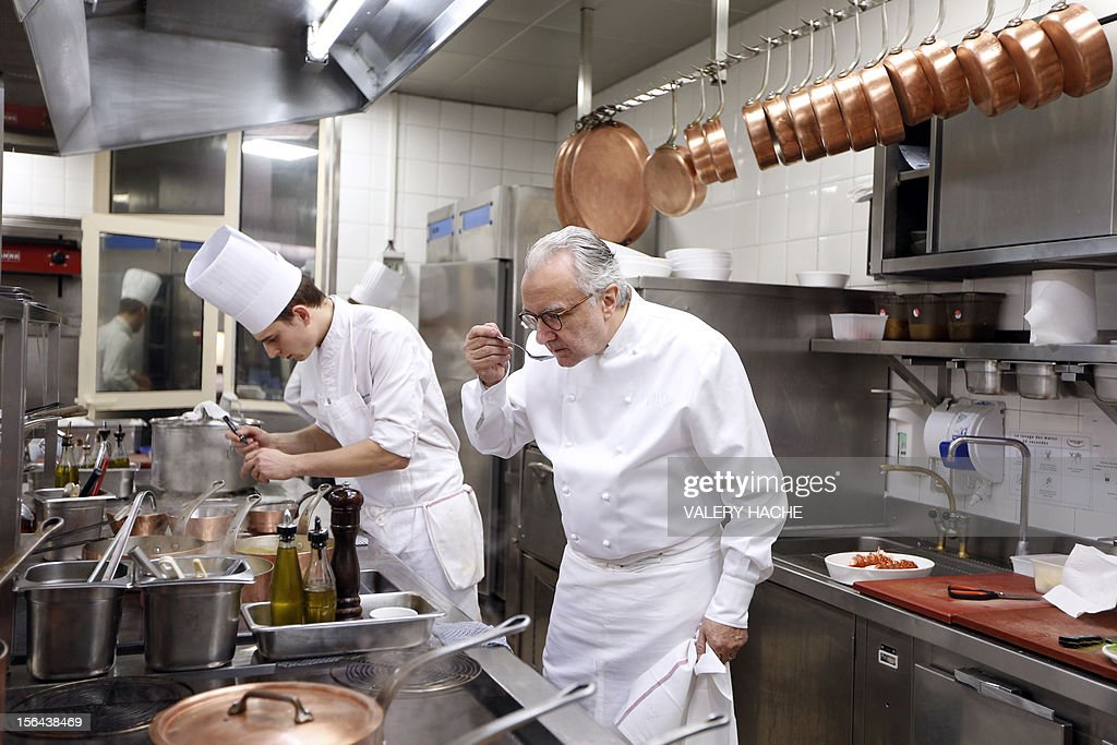 French Alain Ducasse cooks in the kitchen of his 'Louis XV' restaurant in the Hotel de Paris in Monaco which will be celebrating its 25th anniversary. AFP PHOTO / VALERY HACHE