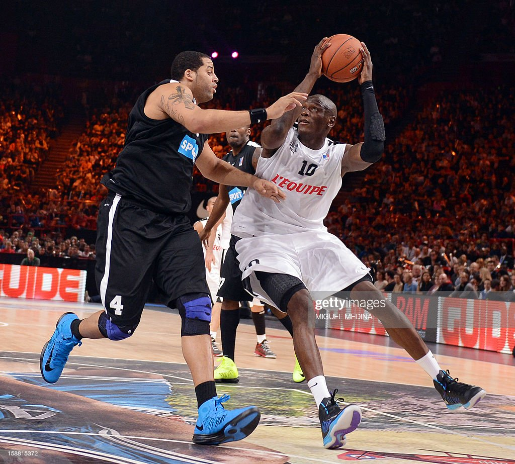 French All star player Amara Sy (R) vies with a Foreign ProA All Star player US Sean May during the France's national basketball league (LNB) 2012 All Star Game on December 30, 2012 at the Palais Omnisport de Paris-Bercy (POPB) in Paris.