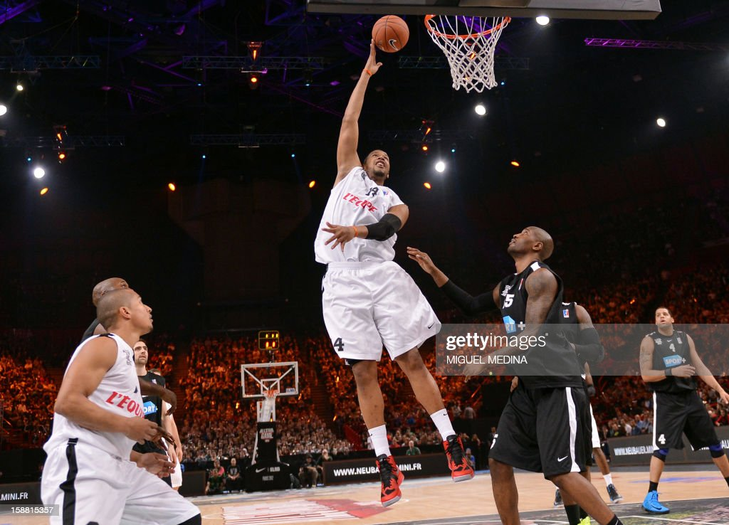 French All star player Ludovic Vaty (C) jumps to score against Foreign ProA All Star player US Jawad William (CR)during the France's national basketball league (LNB) 2012 All Star Game on December 30, 2012 at the Palais Omnisport de Paris-Bercy (POPB) in Paris.