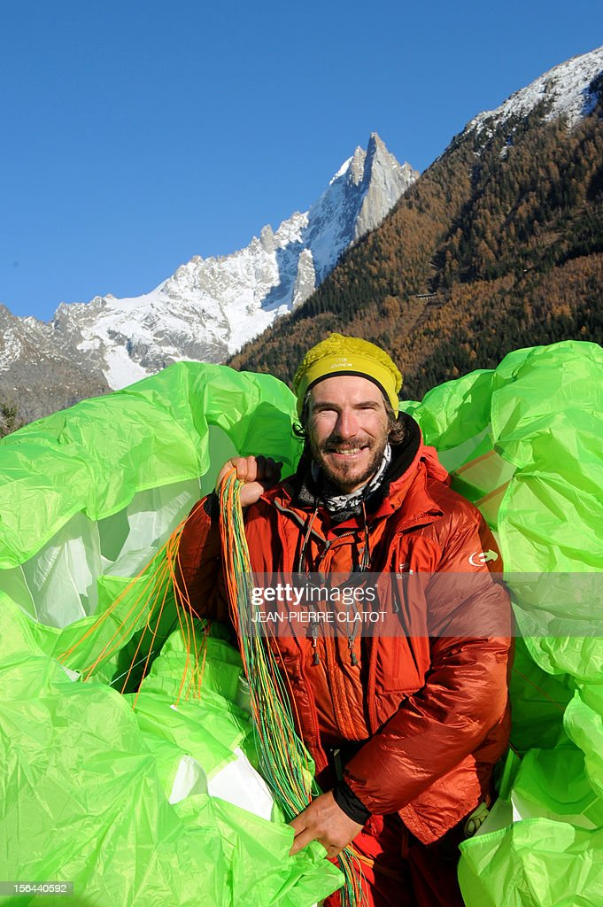 AGASSE - French alpinist Lionel Daudet poses with his paragliding upon his arrival in Chamonix, on November 15, 2012, at the end of his trip around France following coastal and terrestrial borders without any motorized transport, walking more than 5000 km and crossing 1000 mountain tops. AFP PHOTO / JEAN-PIERRE CLATOT
