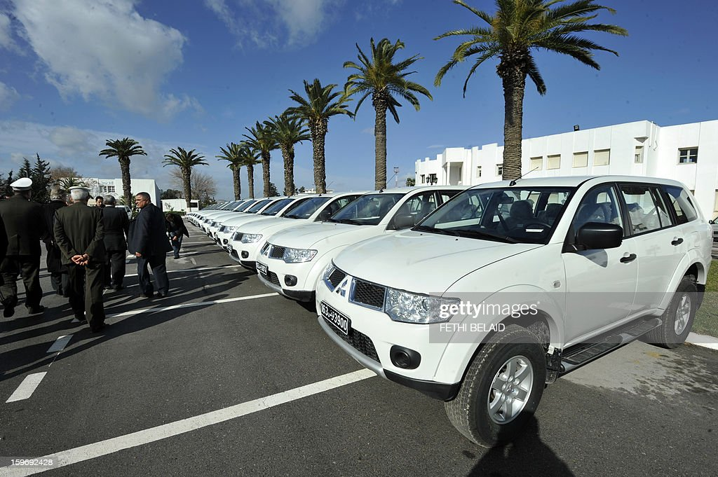 French ambassador in Tunisia and officials walk past cars that France offered to Tunisia to monitor the jihadists on the border of the country on January 18, 2013 outside the barracks of the Tunisian national gendarmerie in Tunis. Tunisian authorities have tightened security measures around the embassy building on the day of the Muslim weekly prayer in the context of the armed intervention of France in Mali.