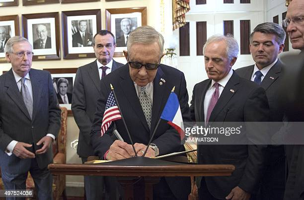 French Ambassador to the US Gerard Araud looks on as Senate Minority Leader Harry Reid DNevada signs a condolence book for the people of France on...
