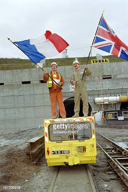 TML French and British workers hold their national flags on December 1 during the historic breakthrough in the Channel Tunnel AFP PHOTO / GERARD FOUET