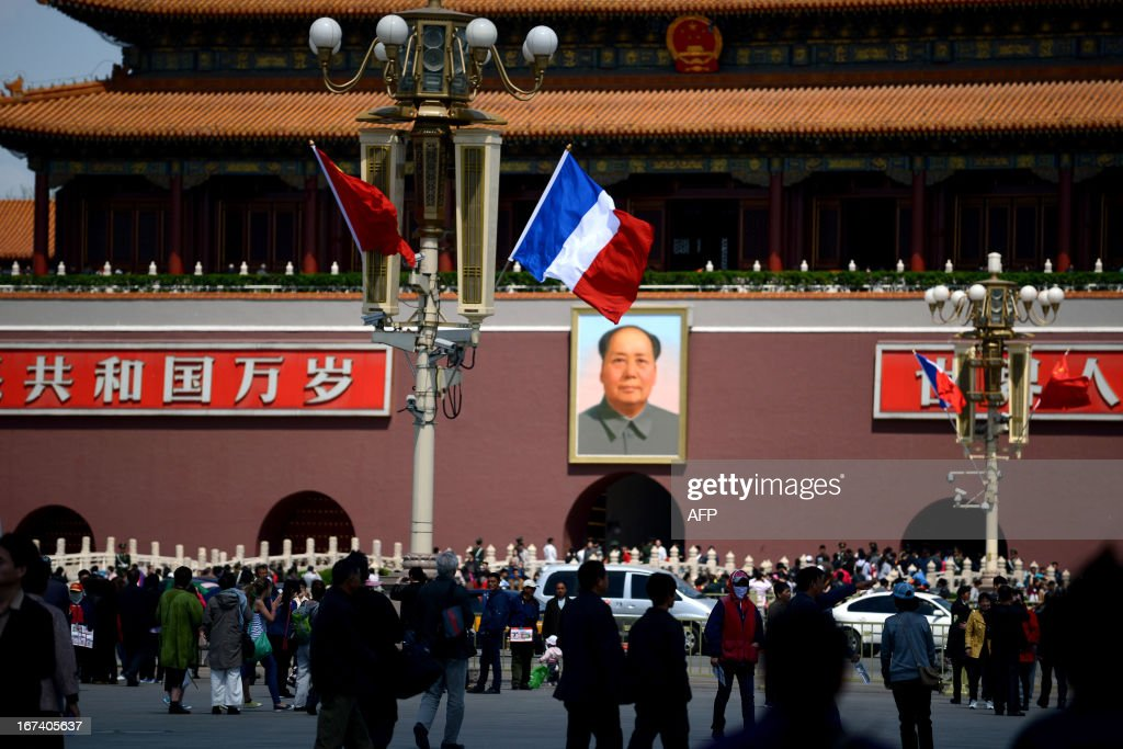 A French (centre R) and Chinese national flag (centre L) hang from a road lamp at Tiananmen square in Beijing on April 25, 2013. French President Francois Hollande arrived in Beijing on April 25 on a trip aimed at boosting exports to China, with hopes that deals can be reached over the sale of aircraft and nuclear power.