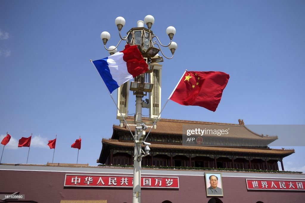 A French (L) and Chinese national flag (R) hang from a road lamp at Tiananmen square in Beijing on April 25, 2013. French President Francois Hollande arrived in Beijing on April 25 on a trip aimed at boosting exports to China, with hopes that deals can be reached over the sale of aircraft and nuclear power.