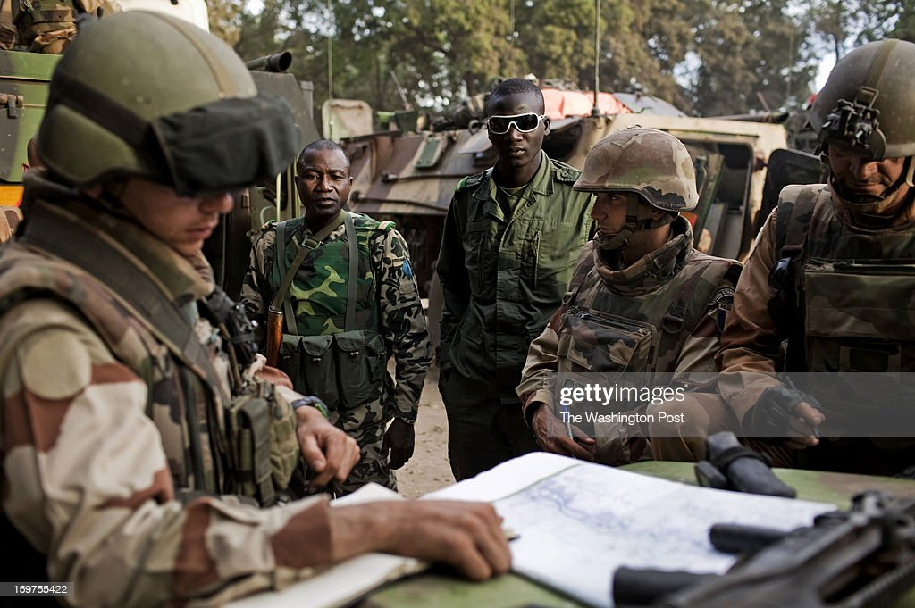 French and Malian soldiers examine maps of the area in the town of Niono, near the frontline, on Saturday, Jan. 19, 2013. Niono serves as the staging ground for combat operations in the nearby town of Diabaly where French and Malian forces battle Islamist rebels.
