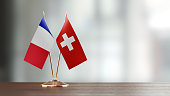 French and Swiss flag pair on desk over defocused background. Horizontal composition with copy space and selective focus.