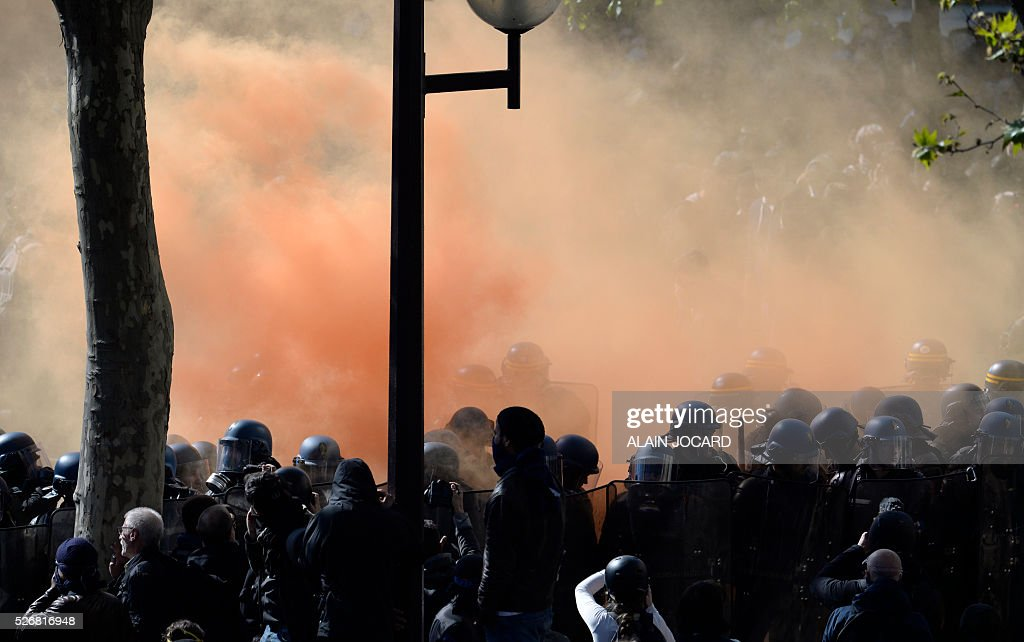 French anti riot police are surrounded by smoke as they face protesters during a clash during the traditional May Day demonstration in Paris on May 1, 2016.