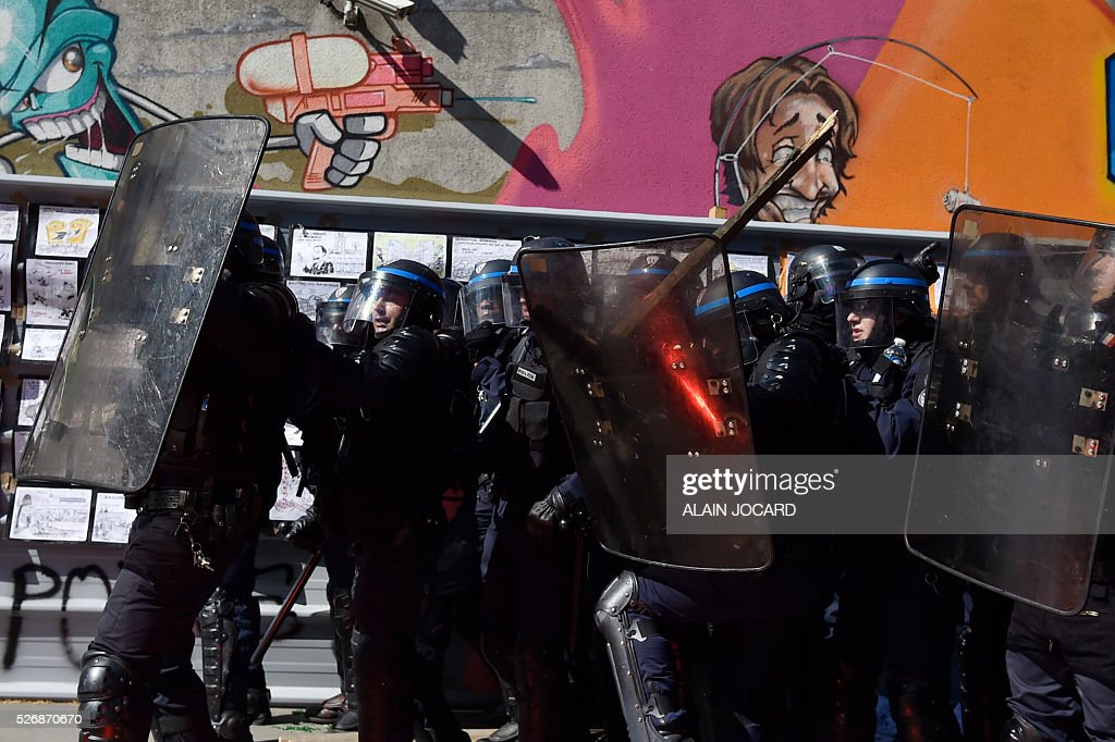 French anti riot police react as a smoke bomb and pieces of wood are thrown during a clash with protesters during the traditional May Day demonstration in Paris on May 1, 2016.