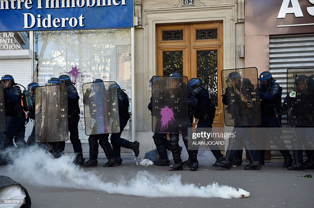 French anti riot police react as smoke bombs are used during a clash with protesters during the traditional May Day demonstration in Paris on May 1, 2016.