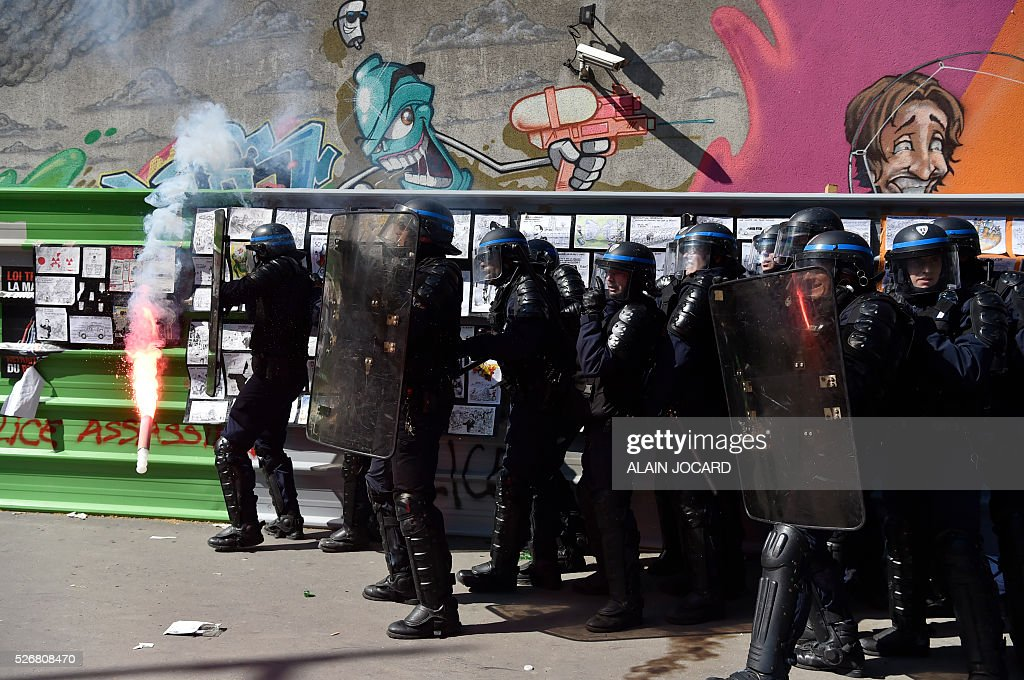 French anti riot police reacts as a smoke bomb is thrown during a clash with protesters during the traditional May Day demonstration in Paris on May 1, 2016.