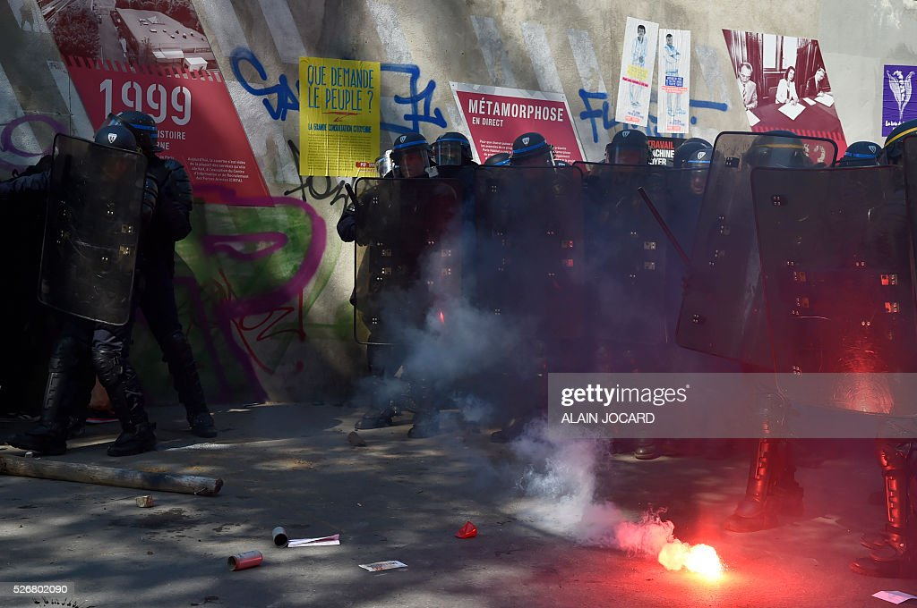 French anti riot police stand with their shields as protesters use flares during a clash during the traditional May Day demonstration in Paris on May 1, 2016.