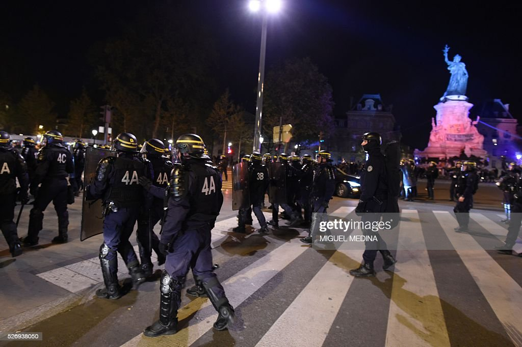 French anti riot policemen walk towards protesters at the Place de la Republique during a protest by the Nuit Debout (Up All Night) movement against the French government's proposed labour reform, on May 1, 2016 in Paris.