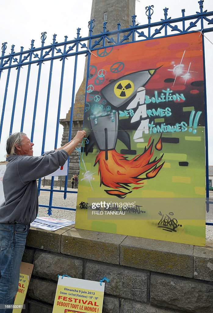 A French anti-nuclear activist fixes a board wich reads : 'Abolition of nuclear weapons' during a protest, on May 6, 2013, in Penmarch, western France, a day after a French test of an M51 submarine-launched ballistic missile failed as it self-destructed off the coast of Brittany. The missile was test fired, without a nuclear warhead, from the Vigilant -- a strategic nuclear submarine -- from the Bay of Audierne and had been due to go down in the isolated north Atlantic. TANNEAU