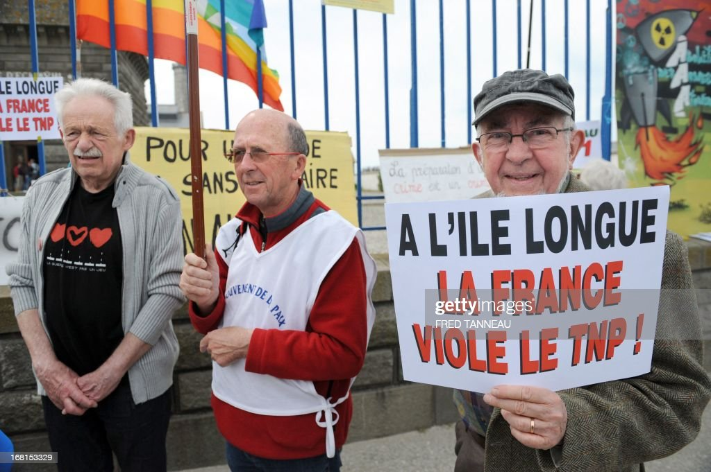 French anti-nuclear activists protest, on May 6, 2013, in Penmarch, western France, a day after a French test of an M51 submarine-launched ballistic missile failed as it self-destructed off the coast of Brittany. The missile was test fired, without a nuclear warhead, from the Vigilant -- a strategic nuclear submarine -- from the Bay of Audierne and had been due to go down in the isolated north Atlantic. The board reads : 'In the Ile longue, France violates the nuclear non-proliferation treaty'. L'Ile longue is a French strategic nuclear submarines base. TANNEAU