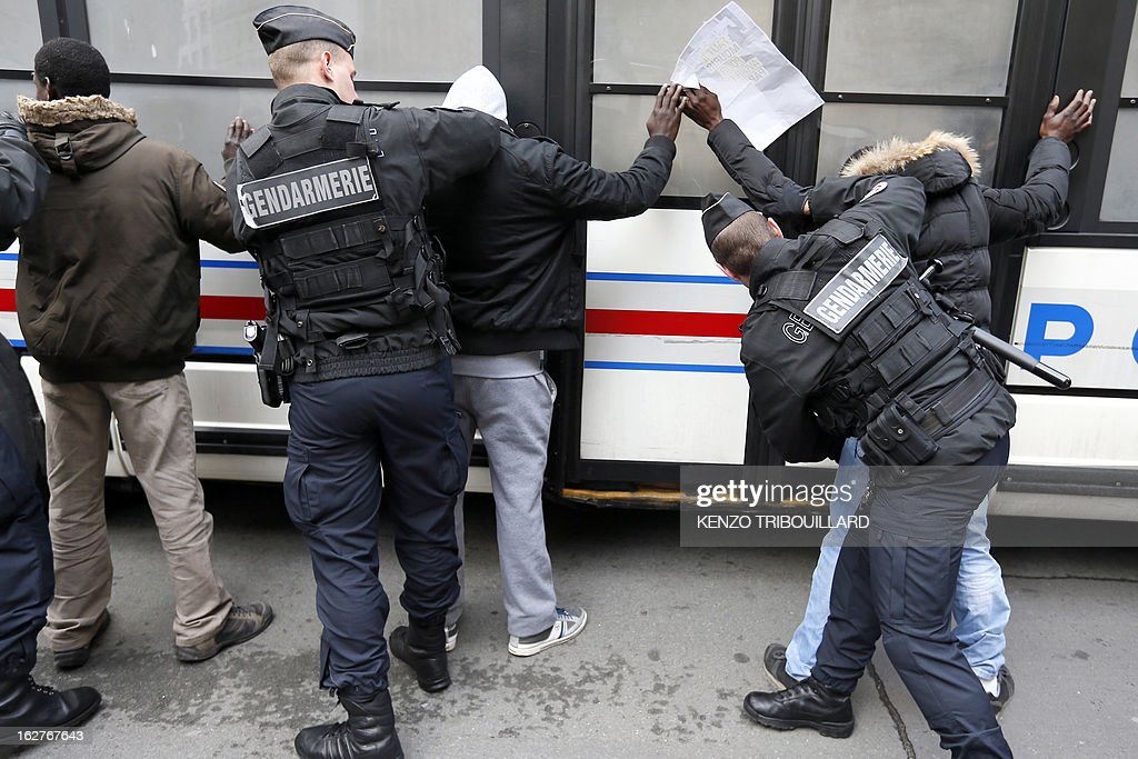 French anti-riot gendarmes frisk illegal immigrants after a demonstration to call for the legalization of all undocumented immigrants in front of the Interior ministry on February 26, 2013 in Paris.