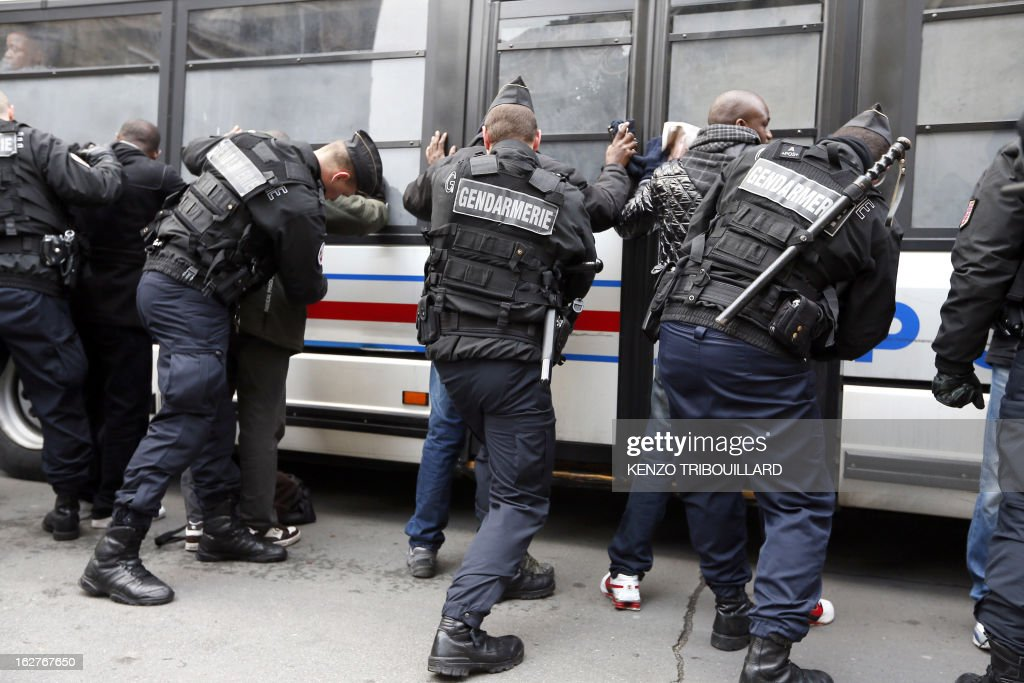 French anti-riot gendarmes frisk illegal immigrants after a demonstration to call for the legalization of all undocumented immigrants in front of the Interior ministry on February 26, 2013 in Paris. AFP PHOTO KENZO TRIBOUILLARD