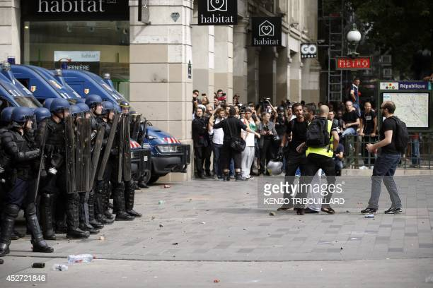 French antiriot police face a proPalestinian supporter held by one of the demonstrator's security staff on the Republique square in Paris during a...