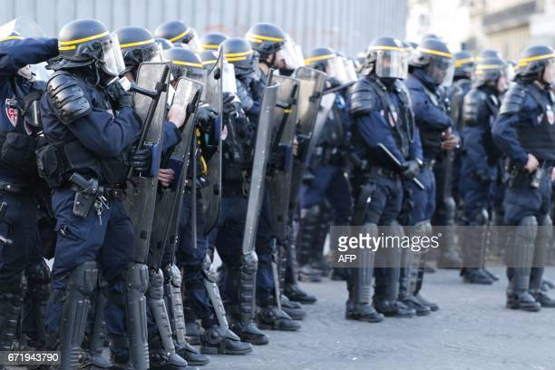French antiriot police forces stand at attention as antifascists demonstrate in Paris on April 23 2017 following the announcement of the results of...