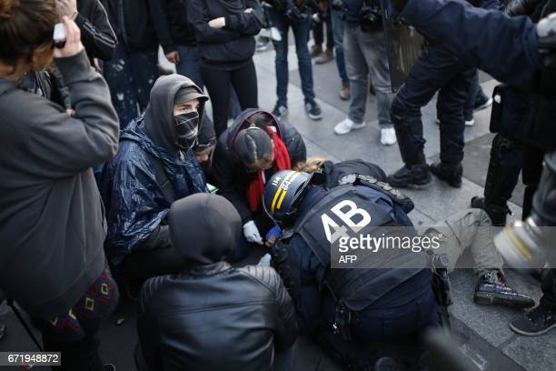 French antiriot police forces tend to a demonstrator lying on the ground in Paris on April 23 2017 following the announcement of the results of the...