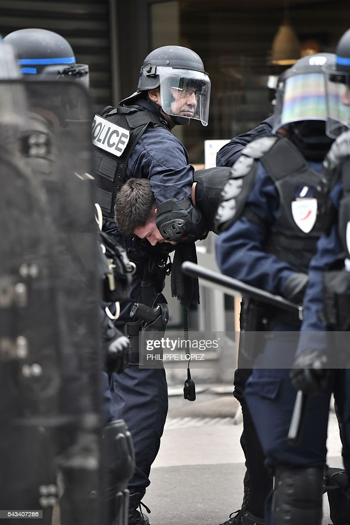 French anti-riot police holds a man during a demonstration against controversial labour reforms, on June 28, 2016 in Paris. Unions have called repeated strikes and marches in opposition to the law, which seeks to bring down France's intractable 10-percent unemployment rate by making it easier to hire and fire workers. / AFP / PHILIPPE