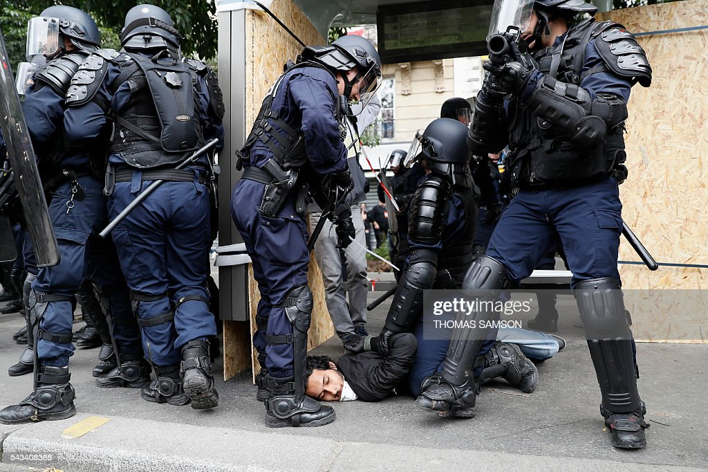 French anti-riot police officer detain a man during a demonstration against controversial labour reforms, on June 28, 2016 in Paris. Unions have called repeated strikes and marches in opposition to the law, which seeks to bring down France's intractable 10-percent unemployment rate by making it easier to hire and fire workers. / AFP / Thomas SAMSON