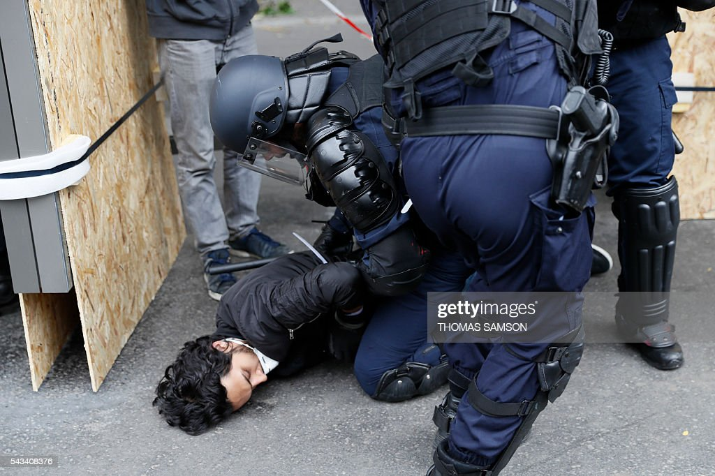 French anti-riot police officers detain a man during a demonstration against controversial labour reforms, on June 28, 2016 in Paris. Unions have called repeated strikes and marches in opposition to the law, which seeks to bring down France's intractable 10-percent unemployment rate by making it easier to hire and fire workers. / AFP / Thomas SAMSON