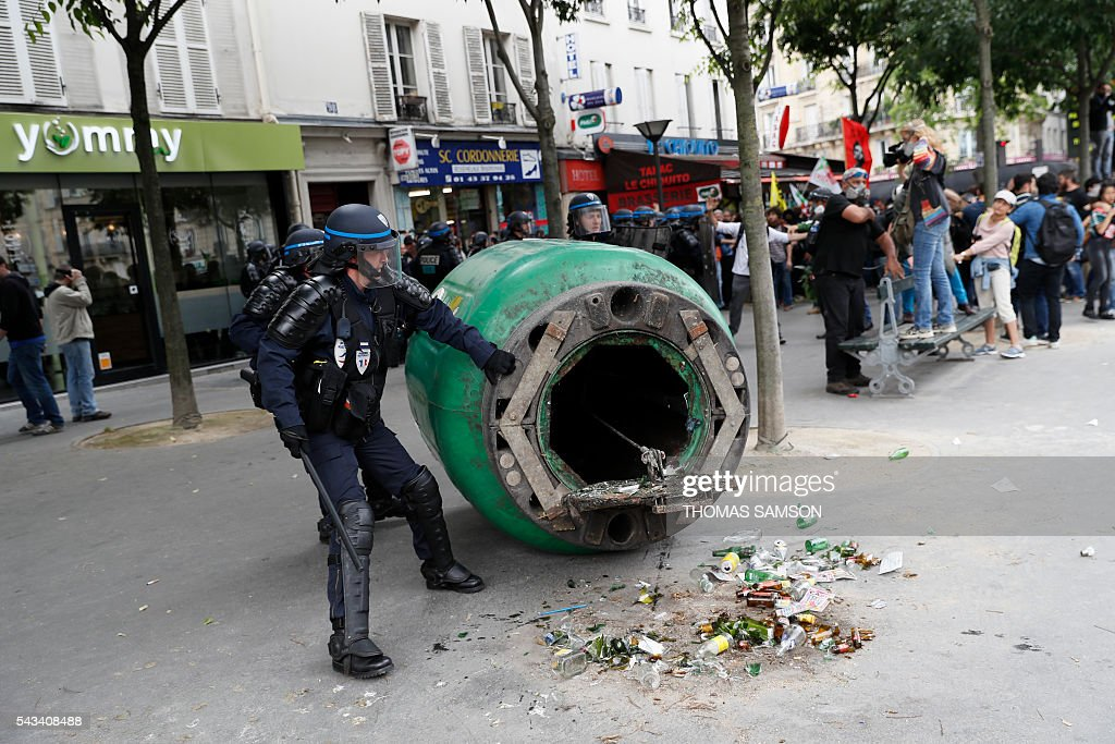 French anti-riot police officers grab a garbage bin thrown accross the sidewalk during a demonstration against controversial labour reforms, on June 28, 2016 in Paris. Unions have called repeated strikes and marches in opposition to the law, which seeks to bring down France's intractable 10-percent unemployment rate by making it easier to hire and fire workers. / AFP / Thomas SAMSON