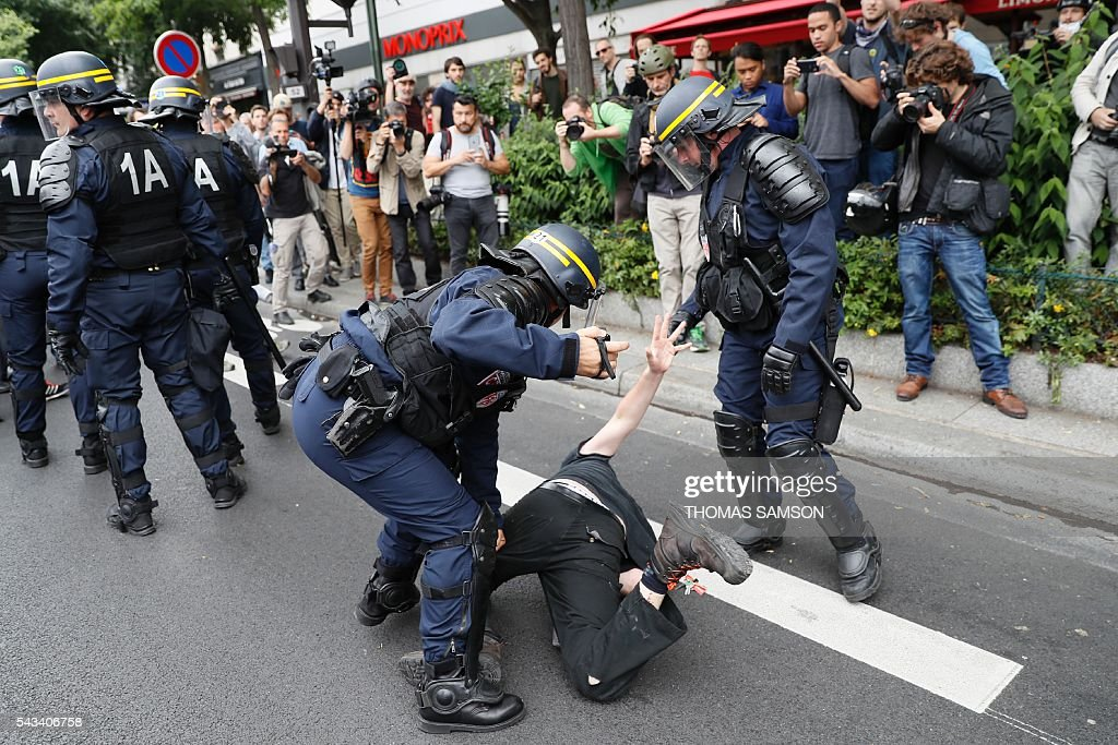 French anti-riot police officers holds a man during a demonstration against controversial labour reforms, on June 28, 2016 on Bastille Square in Paris. Unions have called repeated strikes and marches in opposition to the law, which seeks to bring down France's intractable 10-percent unemployment rate by making it easier to hire and fire workers. / AFP / Thomas SAMSON