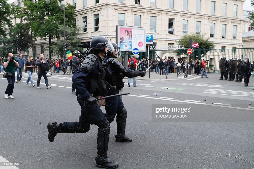 French anti-riot police officers run in front of the Austerlitz train station during a demonstration against controversial labour reforms, on June 28, 2016 in Paris. Unions have called repeated strikes and marches in opposition to the law, which seeks to bring down France's intractable 10-percent unemployment rate by making it easier to hire and fire workers. / AFP / Thomas SAMSON